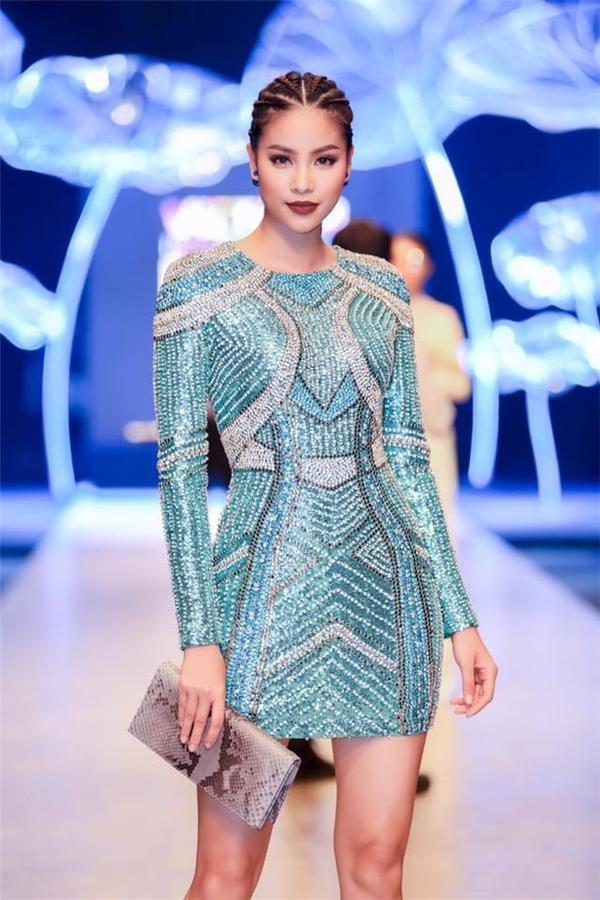 Hoa hậu Hoàn vũ Phạm Hương hóa thân thành nàng chiến binh mạnh mẽ với bộ váy ánh kim ôm sát gợi cảm. Từng mảng họa tiết trên váy đều được bố trí theo cấu trúc bất đối xứng bằng phương pháp thủ công.