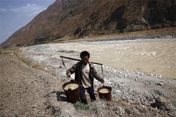 Một người dân xách nước sạch từ 1 con sông trắng xóa ô nhiễm tại quận Đông Xuyên, Côn Minh, Vân Nam, Trung Quốc vào ngày 20/3/2013.