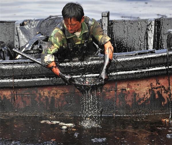 Người công nhân đang vớt dầu tràn gần cảng Đại Liên thuộc tỉnh Liêu Ninh, Trung Quốc. Bức ảnh được chụp 9 ngày sau khi tai nạn vỡ đường ống dẫn dầu xảy ra, khiến 1.500 mét khối dầu thô rò rỉ xuống nước.