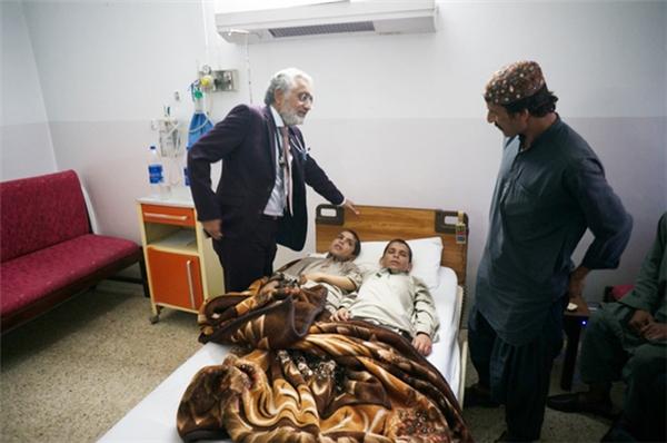 Giáo sư Javed Akram nói chuyện với anh Mohammad Hashim - bố của hai cậu bé.