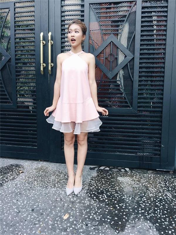 Khả Ngân điệu đà giấu đường cong trong váy chữ A cổ chéo hiện đại. Sắc hồng thạch anh ngọt ngào dường như khá ăn khớp với thân hình mảnh dẻ của cô nàng.
