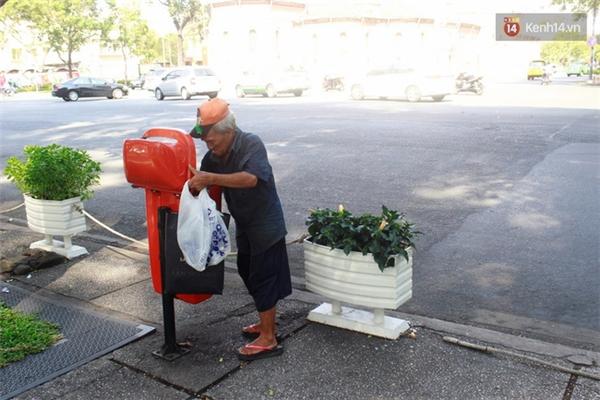 Ông tìm kiếm những chai nước, vỏ lon từ trong thùng rác.