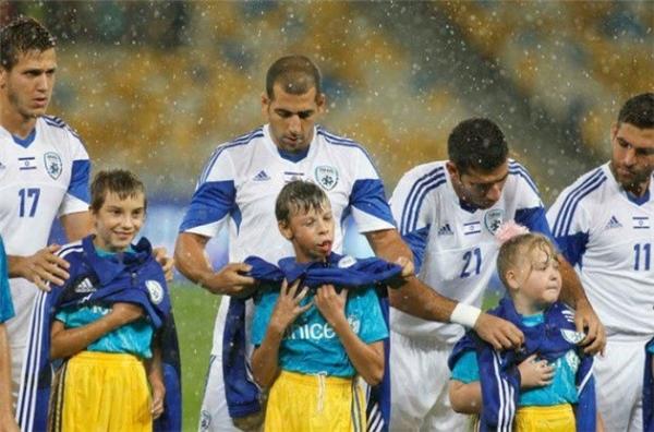 Các cầu thủ bóng đá người Israel đồng loạt cởi áo khoác để che mưa cho những em nhỏ Ukraina trong lễ khai mạc trước trận đấu.