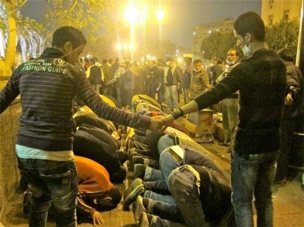 """Những người theo đạo Thiên Chúa nắm tay nhau tạo thành """"lá chắn"""" bảo vệ người Hồi giáo đang cầu nguyện trong một cuộc biểu tình tại Cairo (Ai Cập)."""