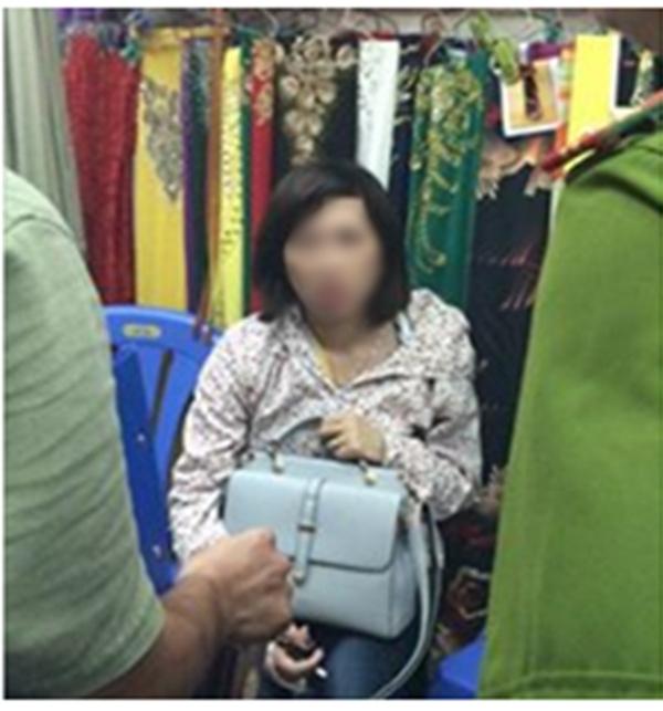 Nữ quái bị chủ tiệm vải bắt quả tang khi đang mở túi lấy trộm ví tiền.