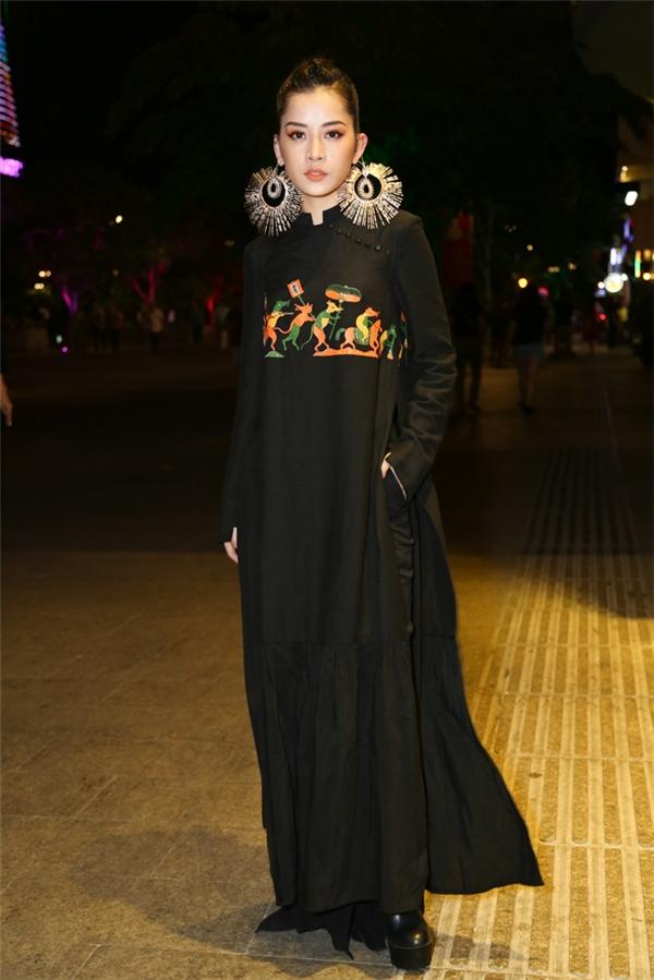 """Chi Pu diện áo dài đen có họa tiết tranh dân gian """"Đám cưới chuột"""". Nữ diễn viên tạo nên sự khác biệt khi kết hợp trang phục truyền thống cùng giày boots đen trên nền chất liệu da."""
