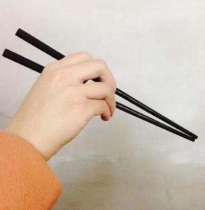 Cách kẹp chắc chắn: Các ngón khép lại với nhau, ngón giữa kẹp ở giữa khoảng không hai chiếc đũa để điều khiển.
