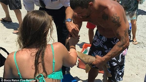 Cảnh cá mập con ngoạm không nhả cẳng tay cô gái dù đã được đưa lên bờ. (Ảnh: Internet)