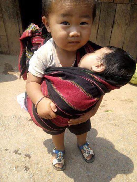 """Đứa bé trai trông rất kháu khỉnh đang địu đứa em nhỏ khiến trái tim cộng đồng mạng như muốn """"tan chảy"""". (Ảnh: Internet)"""