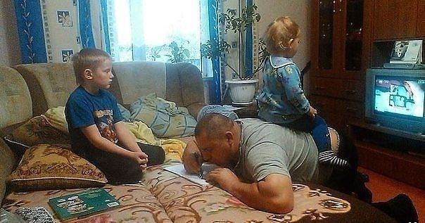 Ông bố của năm: Làm bài tập cho con trai trong khi làm ghế đệm cho con gái. (Ảnh: Internet)