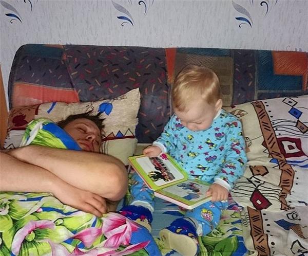 Đến giờ đọc truyện dỗ con ngủ rồi, con tự đọc đi nhé. À, cầm sách ngược rồi, vậy xem tranh đi. (Ảnh: Internet)