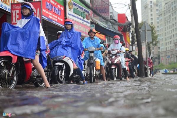 Do lòng đường ngập sâu nên người dân phải xếp hàng, nhích từng chút trên vỉa hè đường Nguyễn Hữu Cảnh.