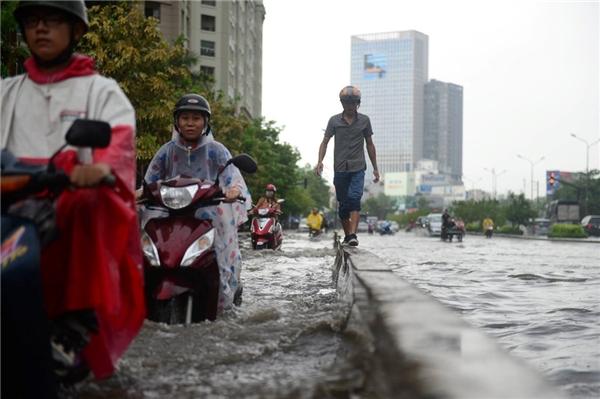 Để tránh nước ngập một thanh niên phải đi bộ trên con lươn phân cách làn xe
