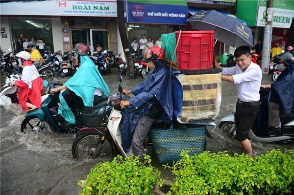 Một nhân viên văn phòng phụ giúp một người đàn ông chở hàng khi xe chết máy trên đường Nguyễn Hữu Cảnh, quận Bình Thạnh