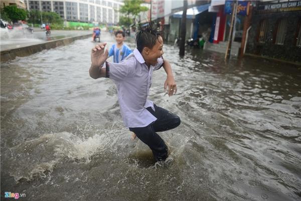 Đây là cơn mưa lớn đầu mùa nên trẻ em rất thích thú, vui đùa giữa dòng nước.