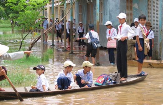 Thậm chí có những ngôi trường bị ngập sau đến mức các em vừa ra khỏi cửa lớp là phải trèo ngay lên đò mà về nhà. (Ảnh: Internet)
