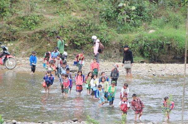 Những đứa trẻ cấp một tội nghiệp phải cùng nhau băng qua sông để đi học trong lúc phải tay xách nách mang nào là cặp sách, tập vở cùng đồ ăn trưa, giày dép. (Ảnh: Internet)