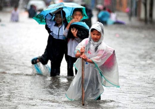 Việc lội nước mưa mà đi vốn đã rất khó khăn, nhất là khi các em phải dùng gậy chống để dò ổ gà trên đường nữa. (Ảnh: Internet)