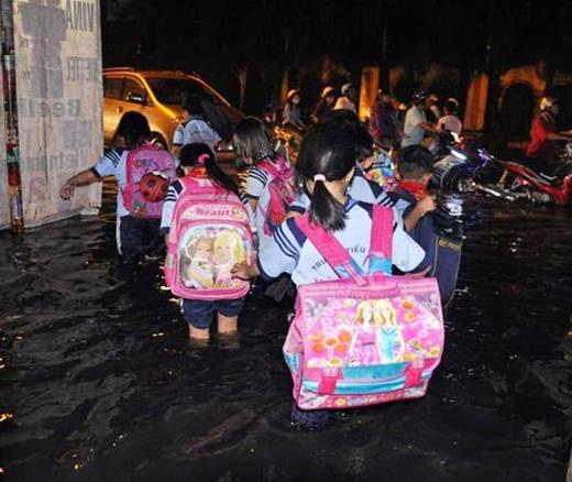 Các em cấp một phải lội qua nước mưa ngập lút đầu gối để ra chỗ bố mẹ đang đậu xe chờ đón về. (Ảnh: Internet)