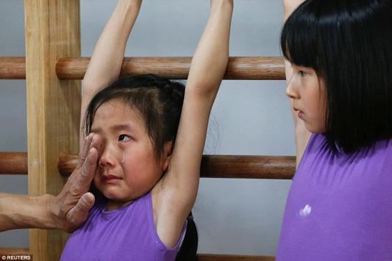 Một bé gái vì quá đau và mệt nên đã bật khóc trong khi vẫn phải tiếp tục bài tập môn thể dục dụng cụ.