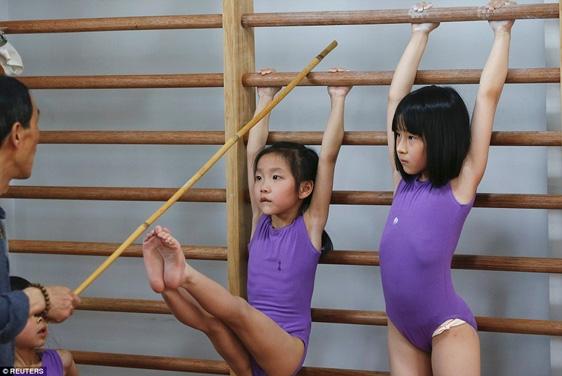 Sau khi lau nước mắt, bé gái tiếp tục thực hiện bài tập vươn chân chạm gậy.
