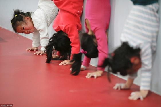 Một số bé gái tập trồng cây chuối tại một ngôi trường thể thao ở Thượng Hải, có em vì đã hết sức nhưng cũng chỉ biết vừa khóc vừa tập.