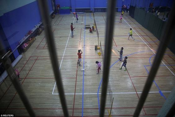 Học sinh đang tập cầu lông tại một trường thể thao ở Bắc Kinh. Đây là ngôi trường có rất nhiều học sinh đã trở thành nhà vô địch Olympic, xung quanh trường treo đầy những tấm poster của họ trên bục huy chương.