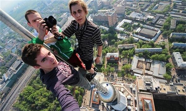 Các thanh niên trèo lên một cột tháp rất cao và hào hứng chụp những tấm ảnh về thành phố phía dưới.