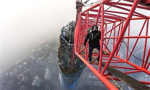 Một thanh niên đi giữa cần cẩu trên đỉnh Tháp Thượng Hải.