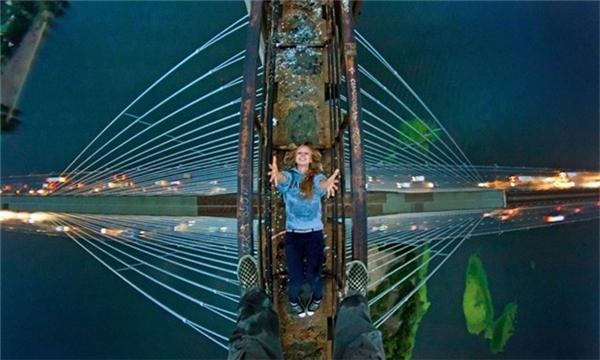 Chàng trai đứng trên nhịp nối của một cây cầu, chụp hình bạn phía dưới.