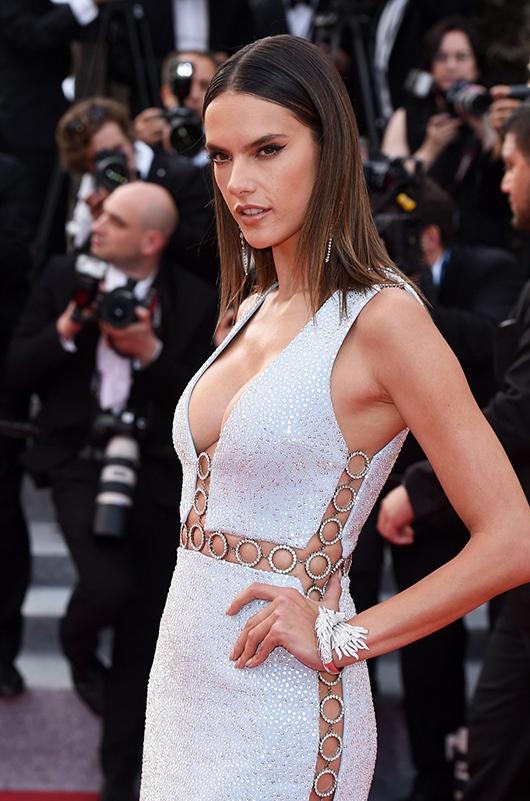 Thiên thần nội y đình đám Alessandra Ambrosio nổi bật trên thảm đỏ với thiết kế màu ánh bạc. Hai bên thân váy và thắt eo được tạo điểm nhấn bằng loạt chi tiết vòng tròn đồng điệu.