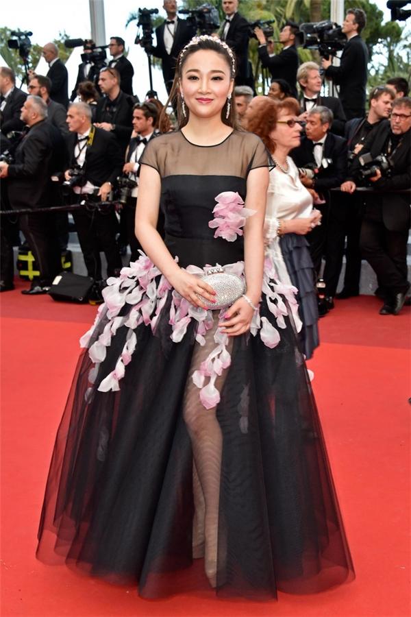 Những bông hoa màu hồng nhạt ngọt ngào trông như đang bị đính kết dở dang trên bộ váy đen.