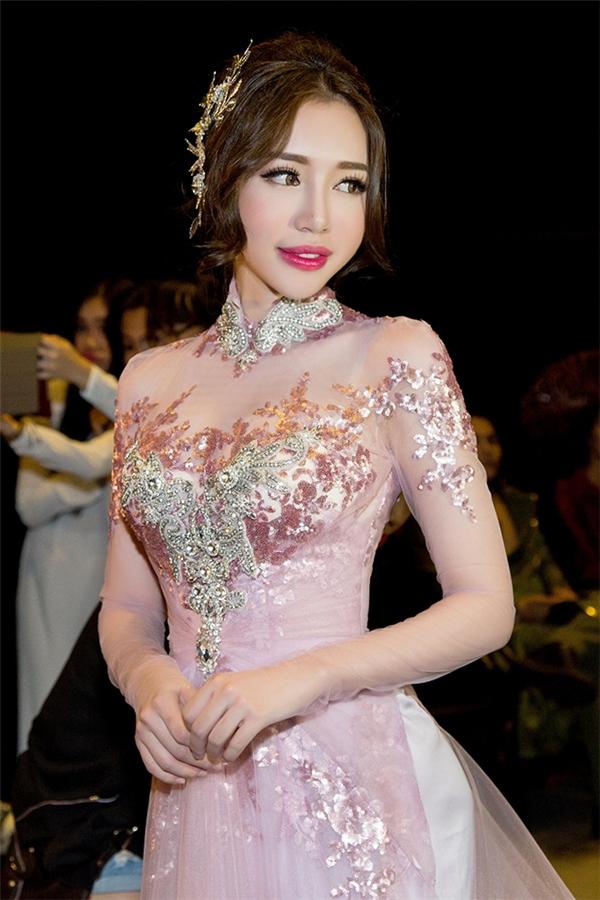 Elly Trần diện áo dài màu hồng ngọt ngào trên nền vải xuyên thấu. Thiết kế được đính kết họa tiết hoa, lá bằng đá, cườm tất kì công. Được biết, chiếc áo dài này có giá khoảng 2.500 USD (tương đương 50 triệu đồng).