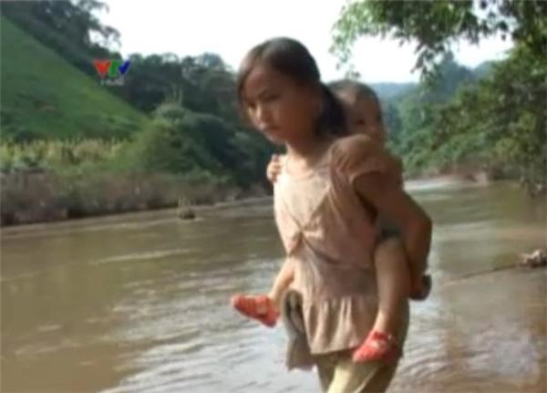 Bé gái đang cõng em lội qua suối. (Ảnh: Internet)