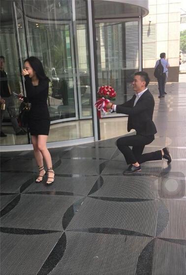 Chàng trai ăn mặc bảnh bao, cầm hoa quỳ gối tỏ tình khiến cô bạn gái rất bất ngờ.