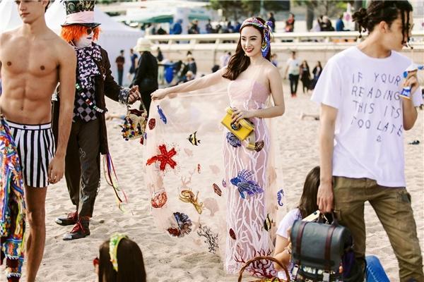 Phần áo choàng của bộ váy tạo điểm nhấn bởi những họa tiết sinh vật biển bằng kĩ thuật thêu tay, đính kết tinh tế.