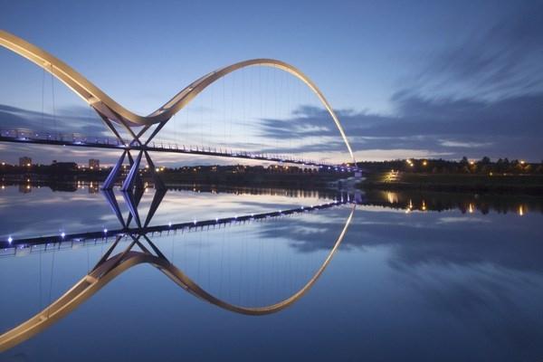 Cầu Infinity (Vô cực), thuộc thị trấn Stockton–on-Tees, Anh, phản chiếu dưới mặt nước trong xanh, tạo nên cấu trúc mái vòm đối xứng hoàn hảo.