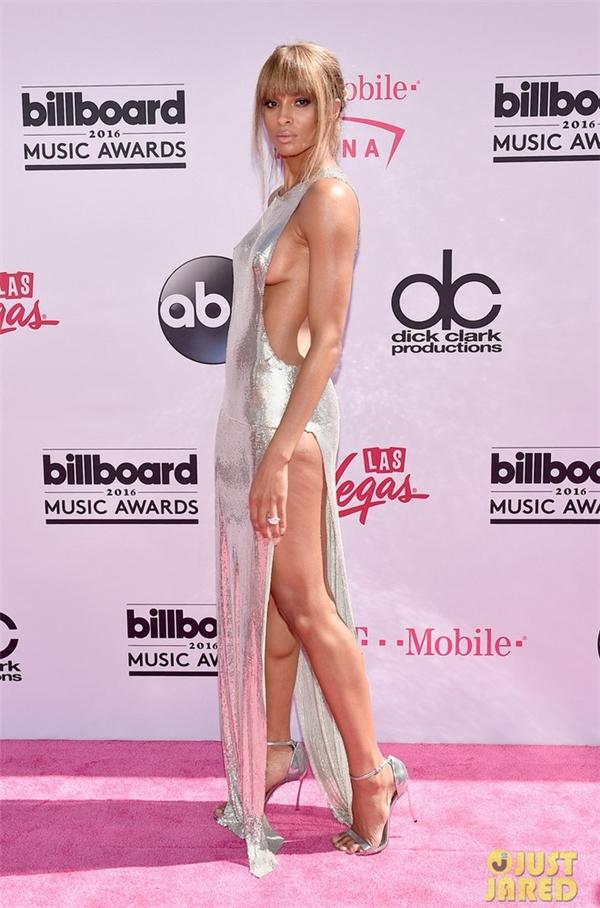 """Trên thảm hồng Billboard 2016, Ciara """"đốt mắt"""" người đối diện khi diện bộ váy ánh kim xẻ cao ở chân, khoét sâu ở lưng. Thật khó để hiểu được, nữ ca sĩ phải diện nội y như thế nào để che chắn."""