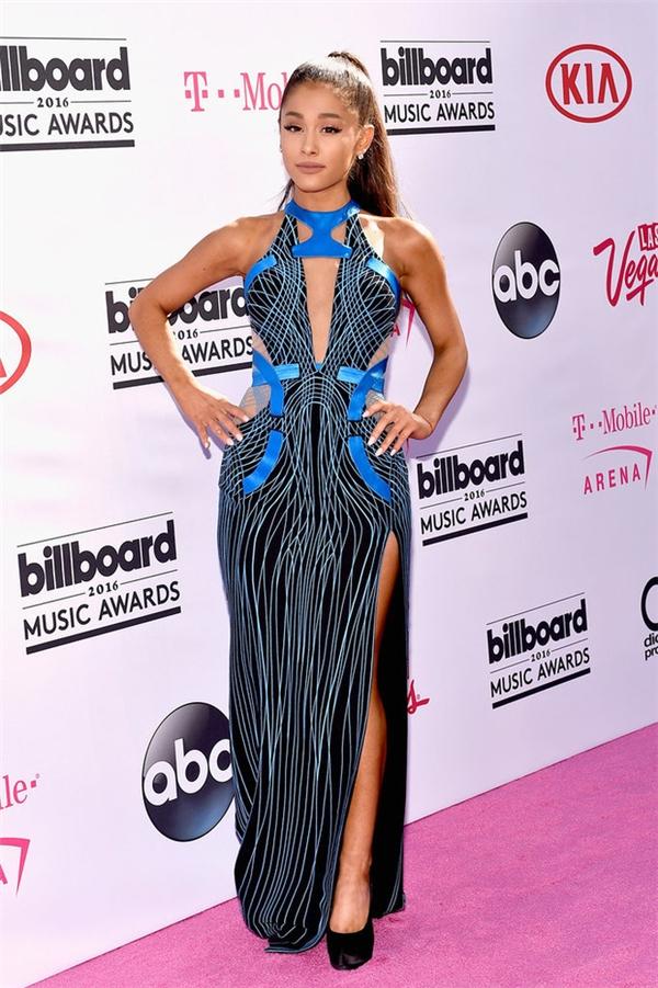 Chiếc đầm với hai tông màu xanh đen của Versace mang lại vẻ ngoài sang trọng, thu hút cho Ariana Grande. Bên cạnh loạt họa tiết trừu tượng, bộ váy còn được tạo điểm nhấn bằng những đường cắt, khoét ở chân, ngực váy.