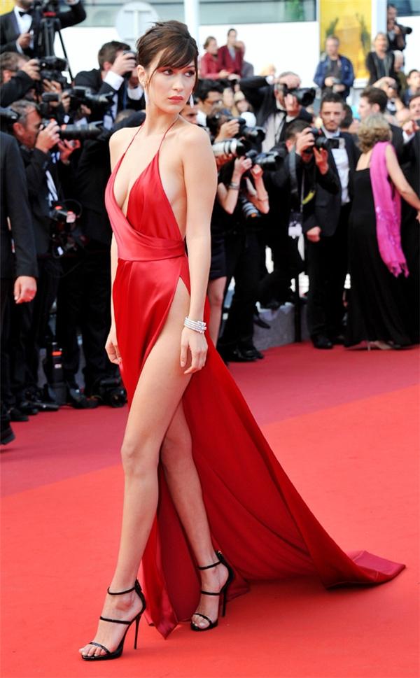 Quay lại với Liên hoan Phim Cannes 2016, Bella Hadid là cái tên được nhắc đến nhiều nhất trong những ngày qua khi diện bộ váy đỏ xẻ tà gần chạm thắt eo. Khi di chuyển lên các bậc thang, chiếc váy khiến nữ người mẫu lúng túng vì dễ xảy ra sự cố lộ hàng. Bella Hadid phải liên tục dùng tay che vùng nhạy cảm.