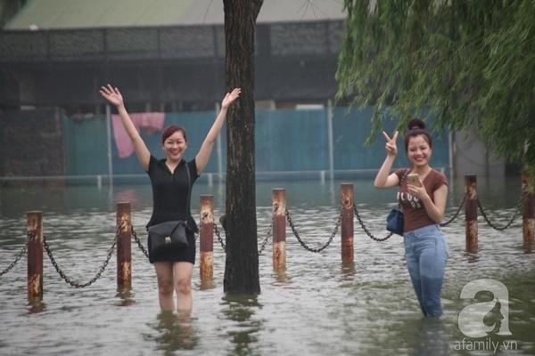 Chỉ là mưa lụt thôi mà, có cần phải phấn khích đến thế không? Ảnh: Lê Bảo