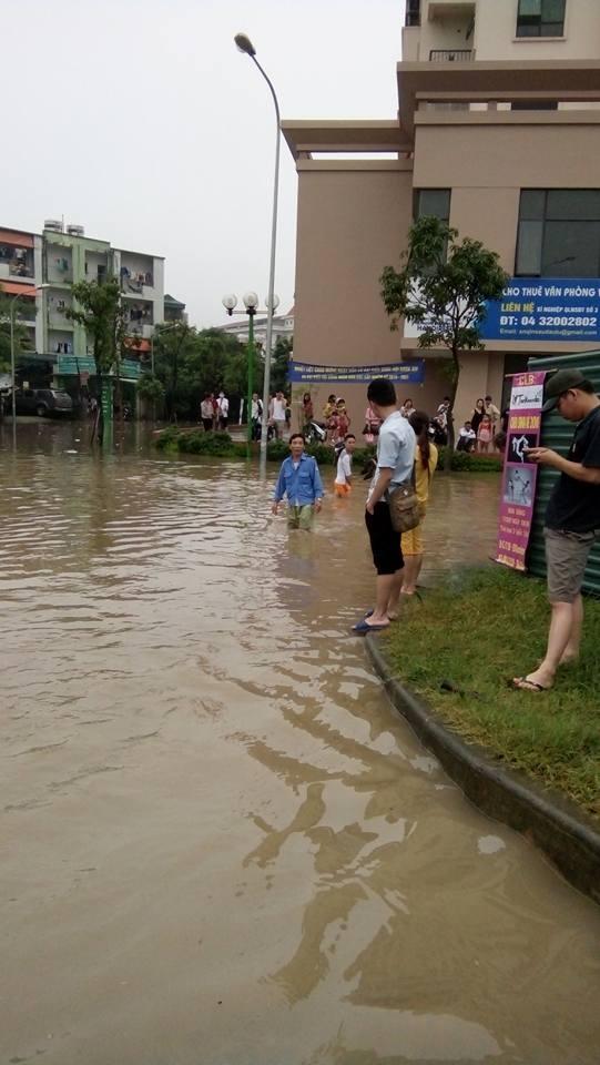 Người dân tại khu đô thị HandiReco trên đường Phạm Văn Đồng phải nhờ tới xe xúc để di chuyển đến trường học, công sở. Đoạn đường ngập nông nhất cũng cao tới trên đầu gối. (Ảnh: Internet)