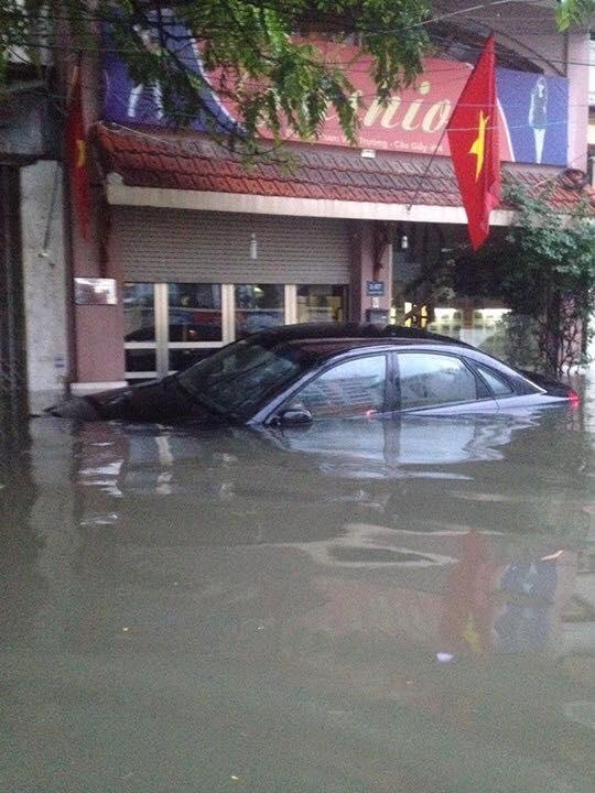 Chiếc ô tô gần nhưchìm lỉm trongbiển nướctạiChợ Nhà Xanh. (Ảnh: Internet)