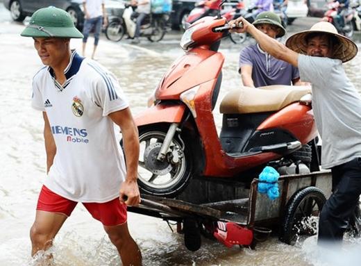 """""""Cõng"""" xe hỏng, chết máy bằng xe ba gác được nhiều người dân tận dụng để phục vụ người đi đường mỗi dịp mưa lớn. Với cách làm này, có thể chở được nhiều xe một lúc. Loại hình dịch vụ này thường có giá từ 100.000 đồng/lần/xe."""