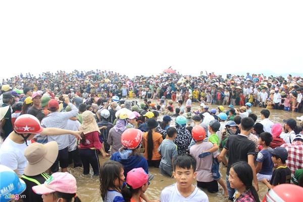 Ở trên bờ có hàng nghìn người dân gồm người lớn và trẻ nhỏ theo dõi.
