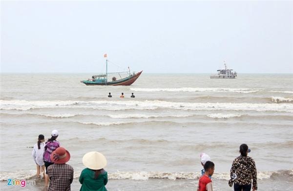 Người dân đứng trong bờ nhìn tàu kéo cá voi ra xa khỏi bờ biển.