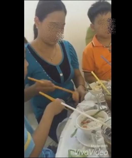 Cậu con trai nhỏcũng cùng mẹ gắp thức ăn bỏ vào túi ni lông. (Ảnh: Cắt clip)