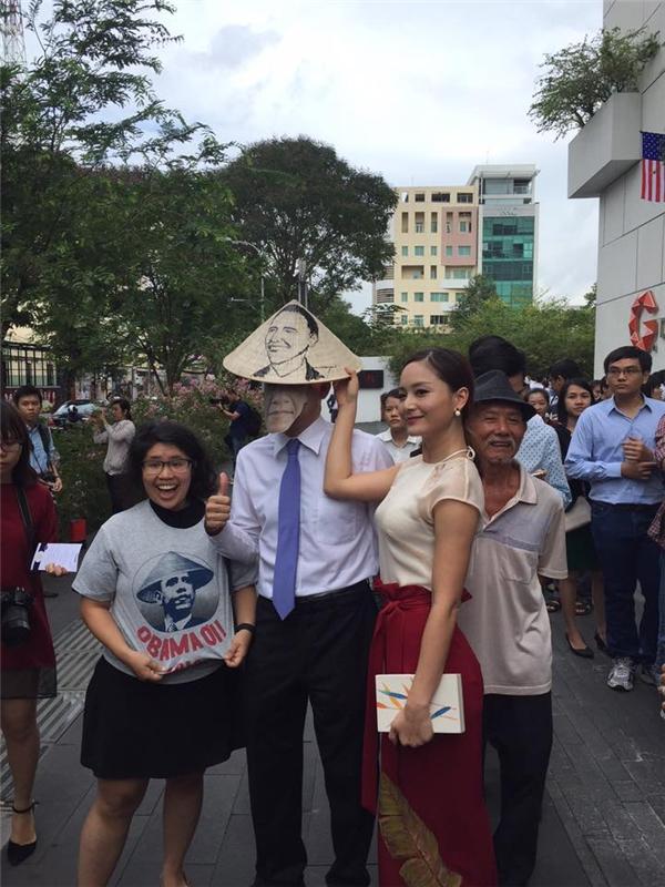 Lan Phương vận chiếc váy đỏ có họa tiết hoa sen và cầm chiếc nón lá có hình ngài Tổng thống, vui vẻ đứng chào đón ông cùng người dân. - Tin sao Viet - Tin tuc sao Viet - Scandal sao Viet - Tin tuc cua Sao - Tin cua Sao