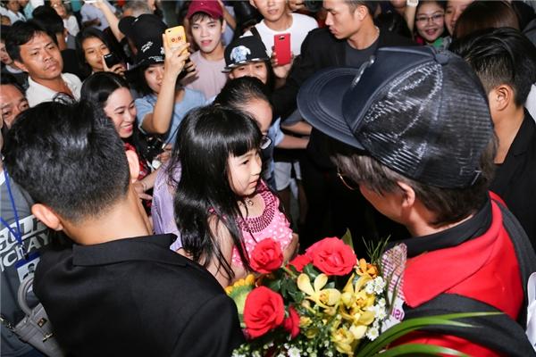 Một fan nhí được ẵm lên để tặng hoa cho thần tượng