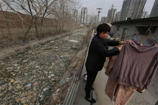 Người dân sống trên bờ sông ngập ngụa rác ở Bắc Kinh, Trung Quốc.